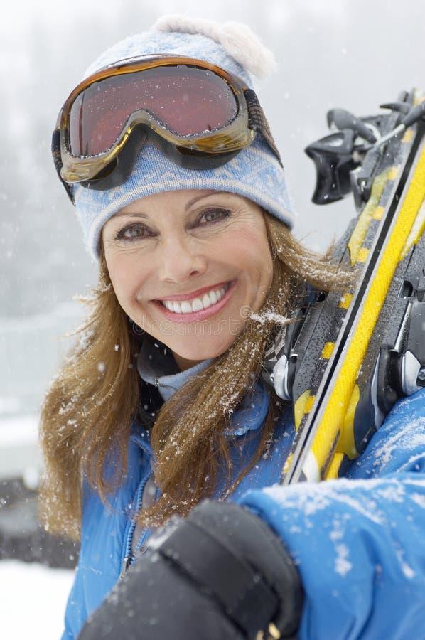 Glückliche reife Frauen-tragender Ski stockbilder