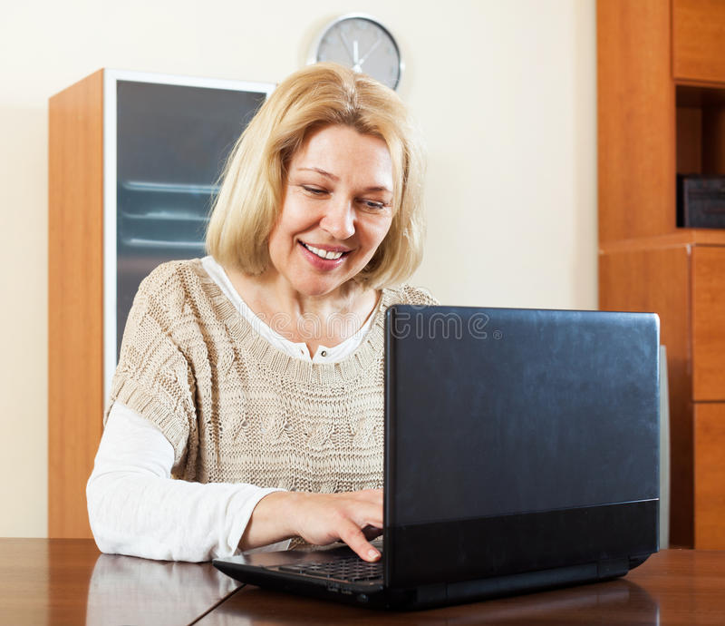 Glückliche reife Geschäftsfrau, die am Laptop im Büro arbeitet lizenzfreie stockfotografie