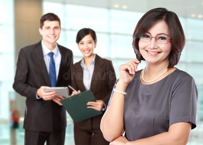 Glückliche reife Geschäftsfrauen mit ihrem Personal hinten lizenzfreies stockbild