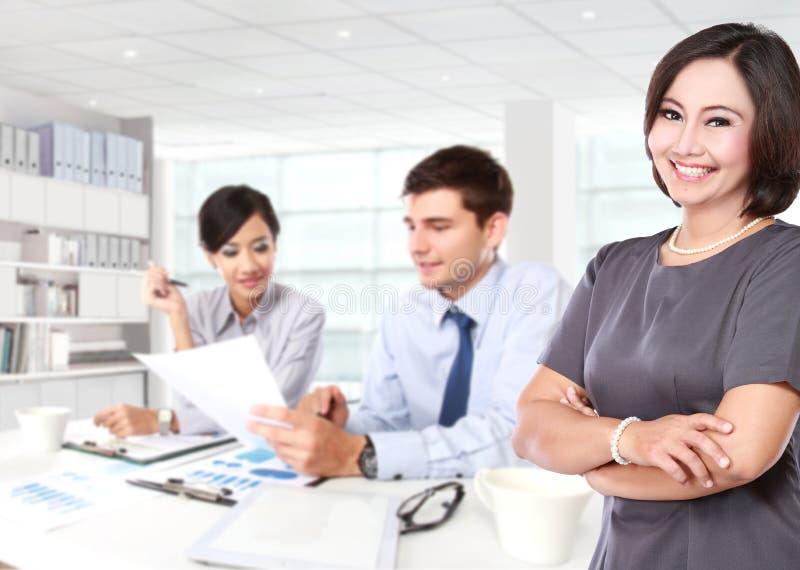 Glückliche reife Geschäftsfrauen mit ihrem Personal zwei hinten stockfotografie