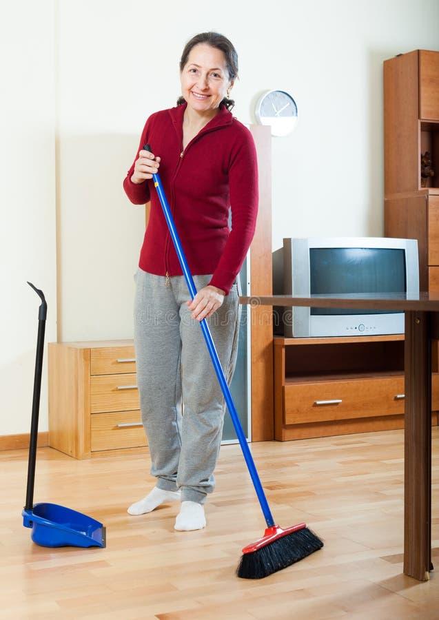 Glückliche reife Hausfraureinigung mit Bürste stockfotografie