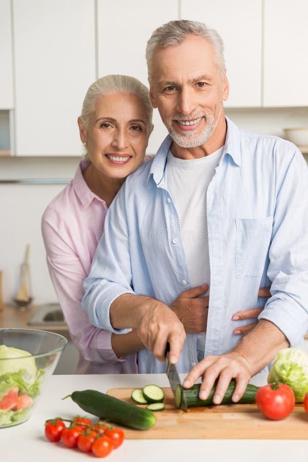 Glückliche reife liebevolle Paarfamilie, die Salat kocht stockfoto