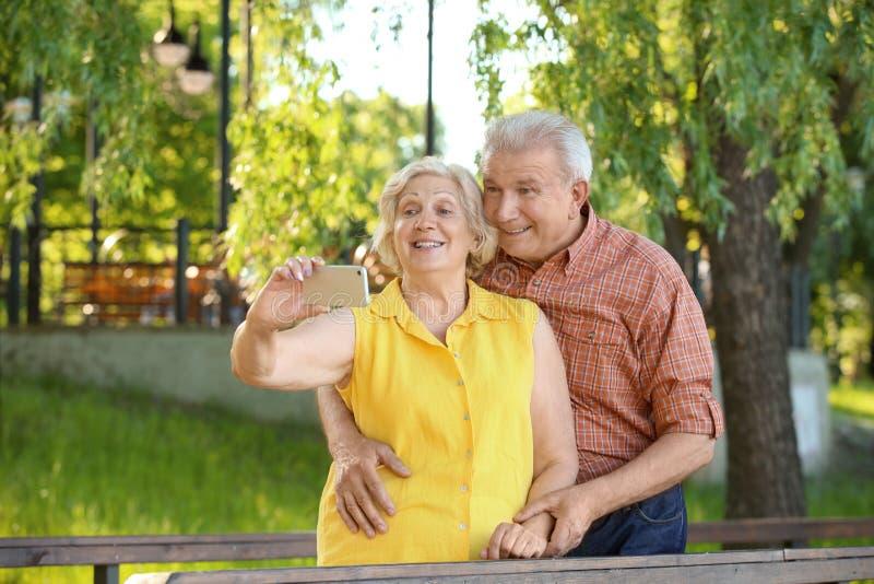Glückliche reife Paare, die selfie im Park nehmen lizenzfreie stockfotos