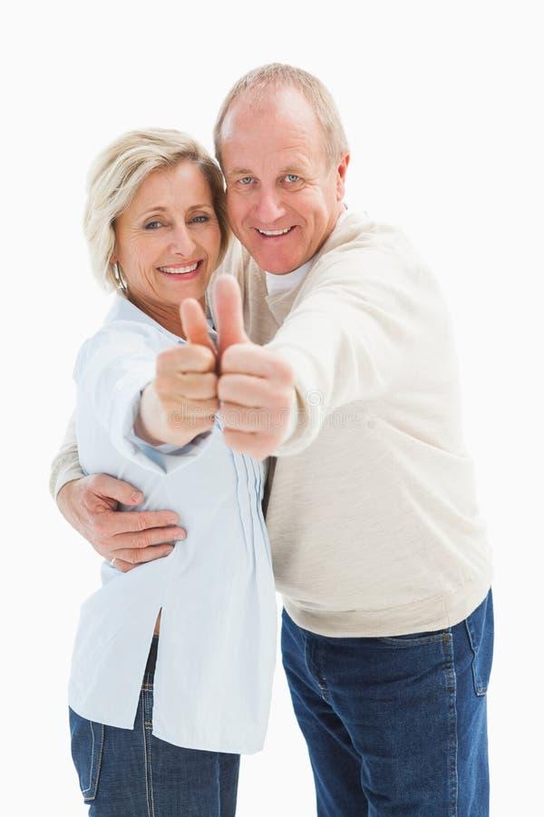 Glückliche reife Paare, die sich Daumen zeigen stockbilder