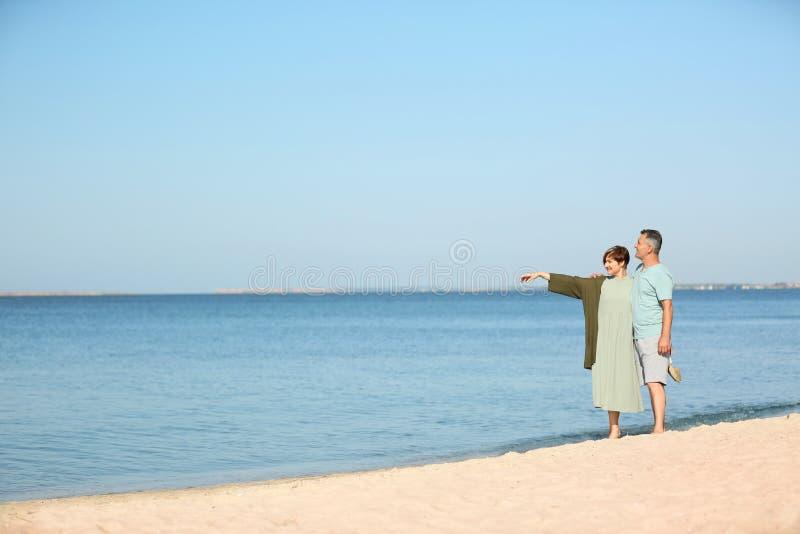 Glückliche reife Paare, die am Strand gehen lizenzfreie stockfotografie