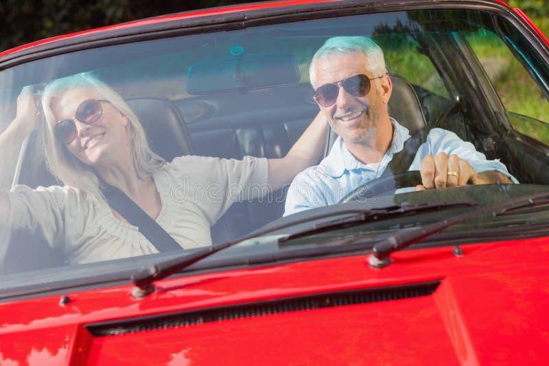 Glückliche reife Paare im roten Cabriolet stockbild