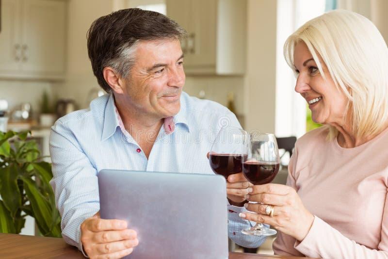 Glückliche reife Paare unter Verwendung der Tablette, die Rotwein trinkt stockfotos