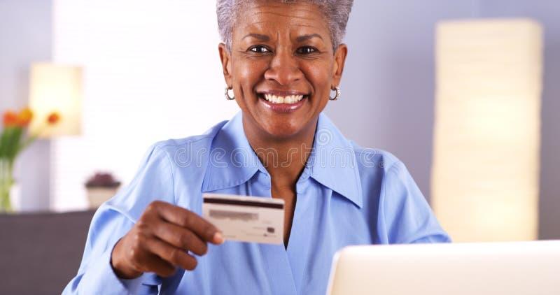 Glückliche reife schwarze Frau, die Kreditkarte hält lizenzfreie stockbilder