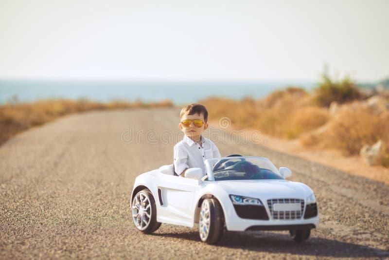 Glückliche Reise des kleinen Jungen mit dem Auto im Sommer stockfotografie
