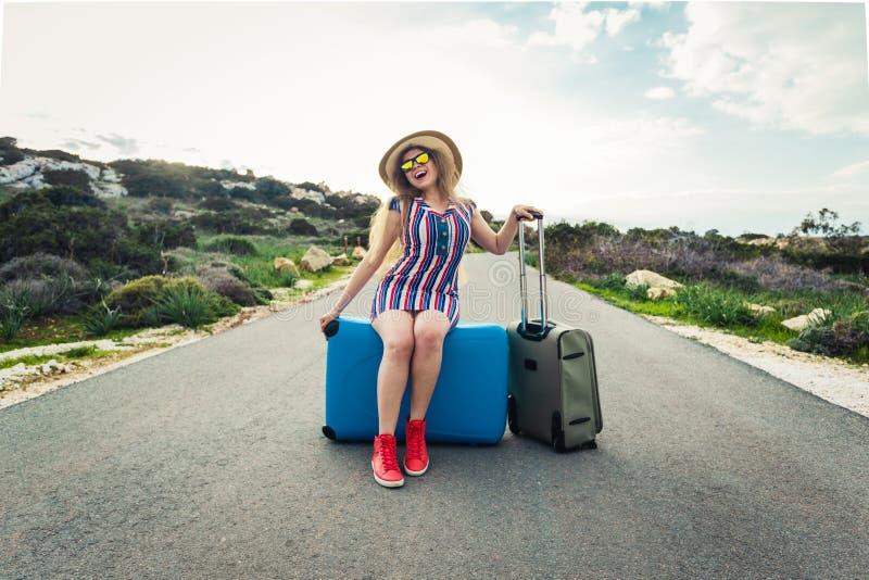 Glückliche Reisendfrau, die auf einem Koffer auf der Straße und dem Lachen sitzt Konzept der Reise, Reise, Reise lizenzfreies stockfoto