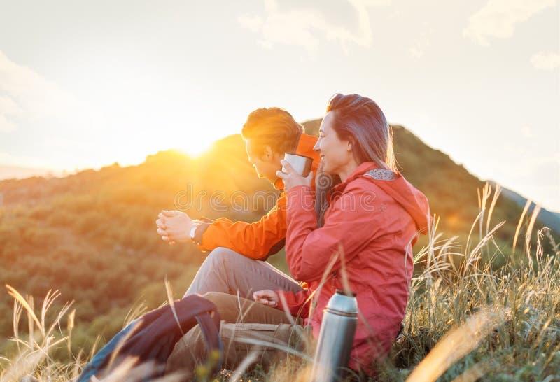 Glückliche Reisendpaare, die in den Bergen bei Sonnenuntergang stillstehen lizenzfreie stockfotos