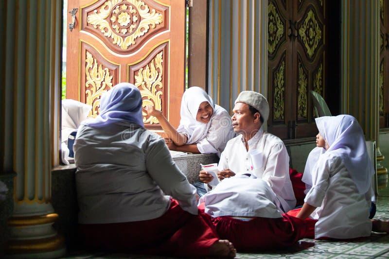 Glückliche reizende moslemische junge Mädchen in der traditionellen Kleidung mit männlichem moslemischem Lehrer innerhalb der Mos stockfotografie