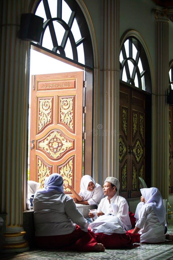 Glückliche reizende moslemische junge Mädchen in der traditionellen Kleidung mit männlichem moslemischem Lehrer innerhalb der Mos lizenzfreie stockfotos