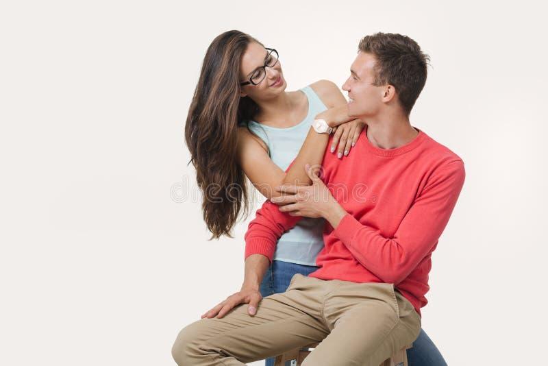 Glückliche reizende Paare, die jedes zu anderem an weißem Hintergrund schauend umarmen und lächeln lizenzfreie stockfotografie