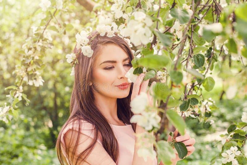 Glückliche riechende Blumen der jungen Frau im Blütenfrühling blüht stockbild
