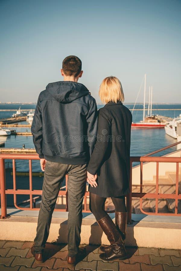 Glückliche romantische attraktive junge Paare, die zusammen draußen am Pier, Hafen bleiben lizenzfreie stockfotografie