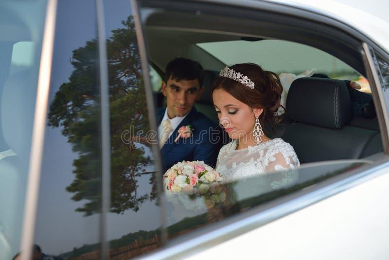 Glückliche romantische Jungvermählten, Braut und Bräutigam, die im Hochzeitsauto sitzt stockfotos