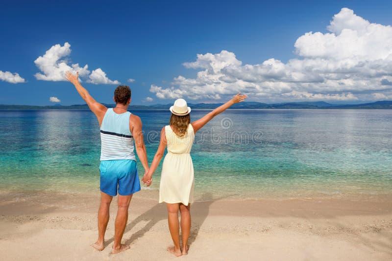 Glückliche romantische Paare, die Ansichttrauminseln auf Strand genießen stockbild