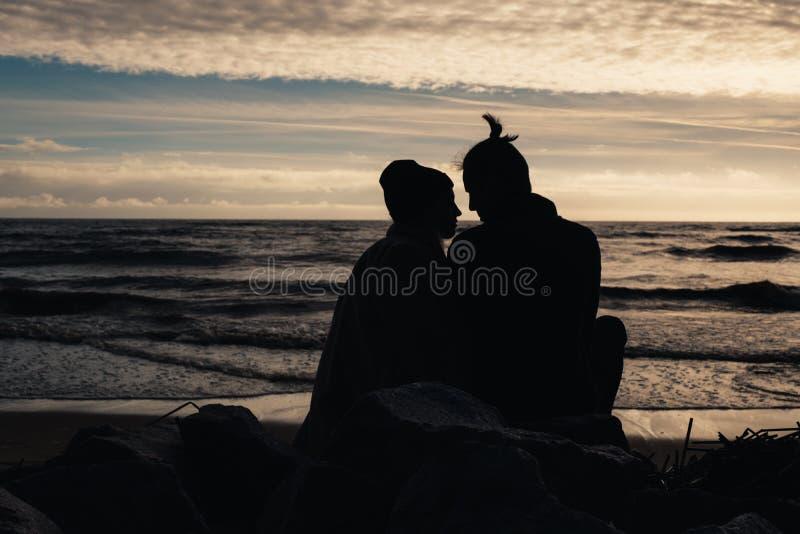 Glückliche romantische Paare, die auf dem Strand nahe Ozean, Entspannung, halten um einander sitzen stockfotos