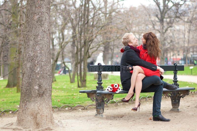 Glückliche romantische Paare, die auf einer Bank umarmen stockfotografie