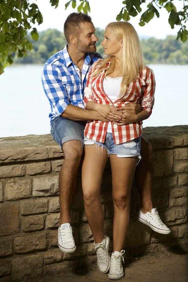 Glückliche romantische Paare, die am Flussufer umfassen stockbild