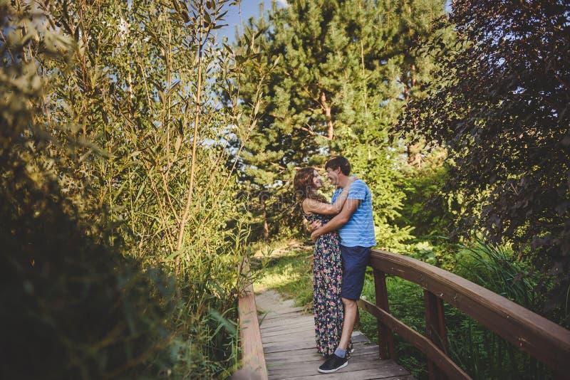Glückliche romantische Paare im Dorf, Spaziergang auf der Holzbrücke Junge Schönheit und Mann, die sich umarmt lizenzfreies stockfoto