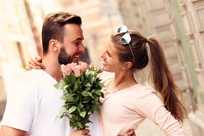 Glückliche romantische Paare mit Blumen lizenzfreie stockfotos