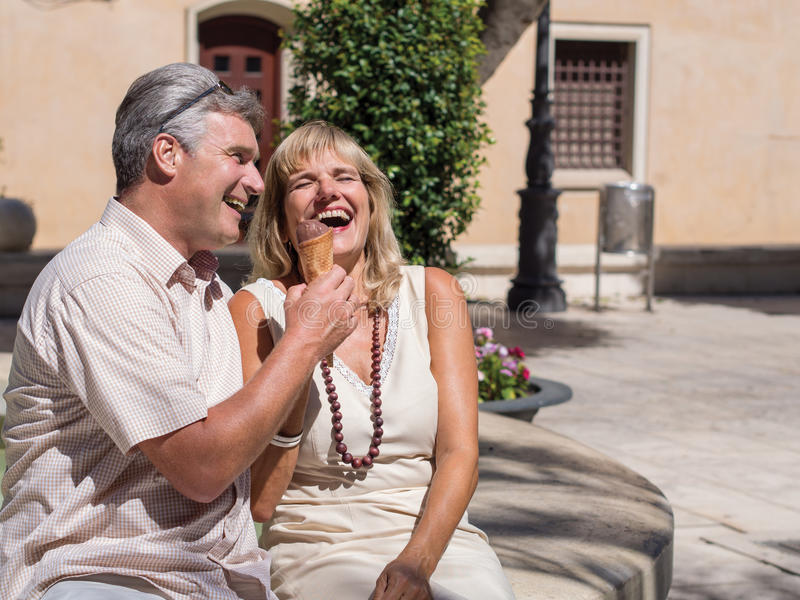Glückliche romantische reife Paare, die über einen guten Witz mit Eiscreme lachen lizenzfreie stockfotografie