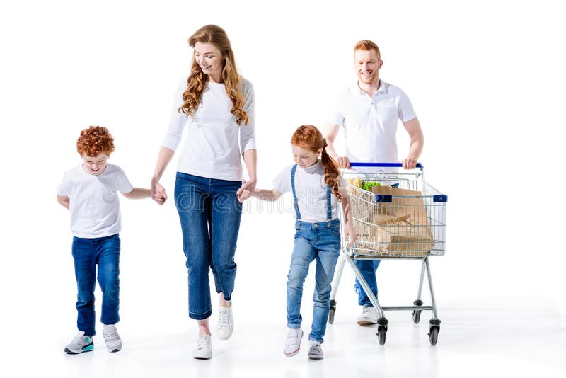 glückliche Rothaarigefamilie mit zwei Kindern, die mit Einkaufslaufkatze gehen stockfotos