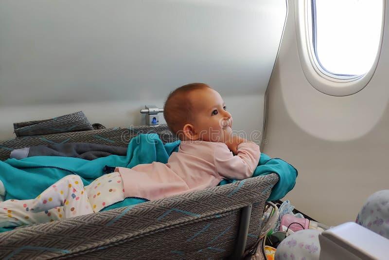 Glückliche Säuglingsbabylaugen in der speziellen Korbwiege im Flugzeug an seinem Magen Erstflug des Babys, wird sie als das Zahne lizenzfreie stockfotografie