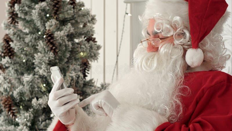 Glückliche Santa Claus, die herauf Weihnachts-E-Mail von den Kindern an seinem Telefon überprüft stockbilder