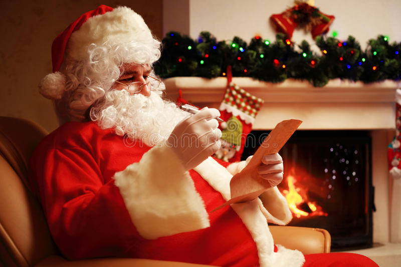 Glückliche Santa Claus, die zu Hause an seinem Raum nahe Weihnachtsbaum und großem Sack sitzt und Weihnachtsbrief oder Wunschlist stockfotografie