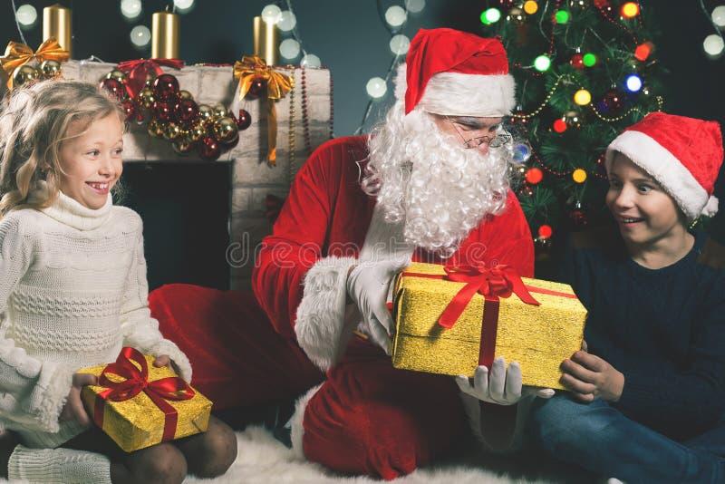 Glückliche Santa Claus und Kinder um den verzierten Weihnachtsbaum lizenzfreie stockfotografie