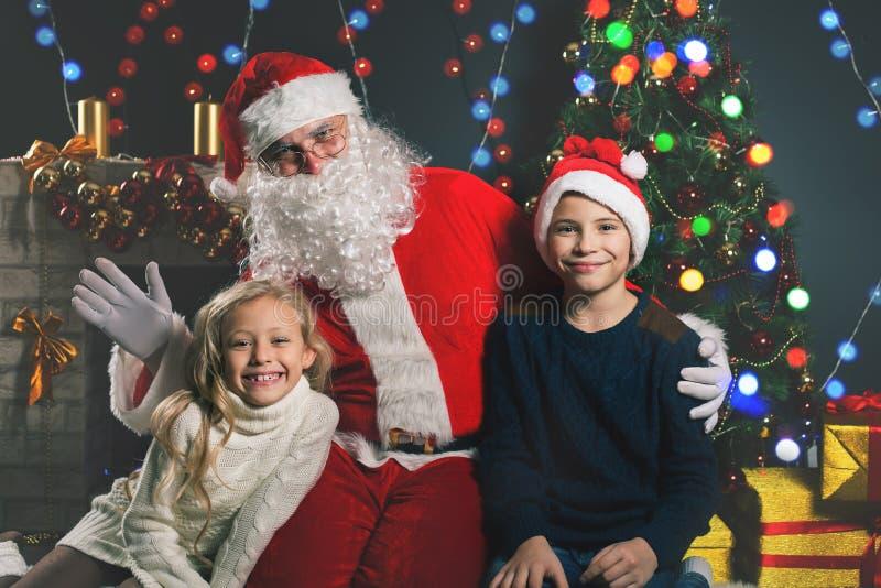 Glückliche Santa Claus und Kinder um den verzierten Weihnachtsbaum stockfotos