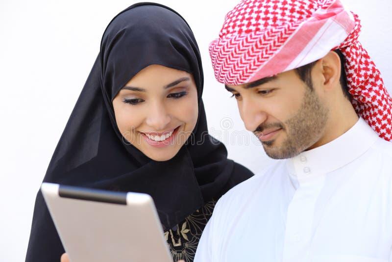 Glückliche saudi-arabische Paare, die zusammen eine Tablette schauen lizenzfreie stockfotografie