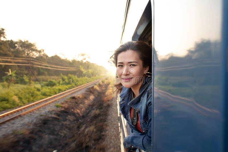 Glückliche schöne Asiatin, die mit dem Zug heraus schaut vom Fenster reist lizenzfreies stockfoto