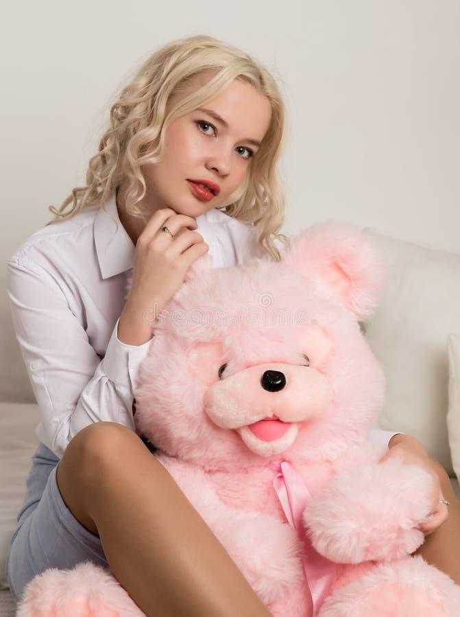 Glückliche schöne Blondine, die einen Teddybären umarmen Konzept des Feiertags oder des Geburtstages stockfoto