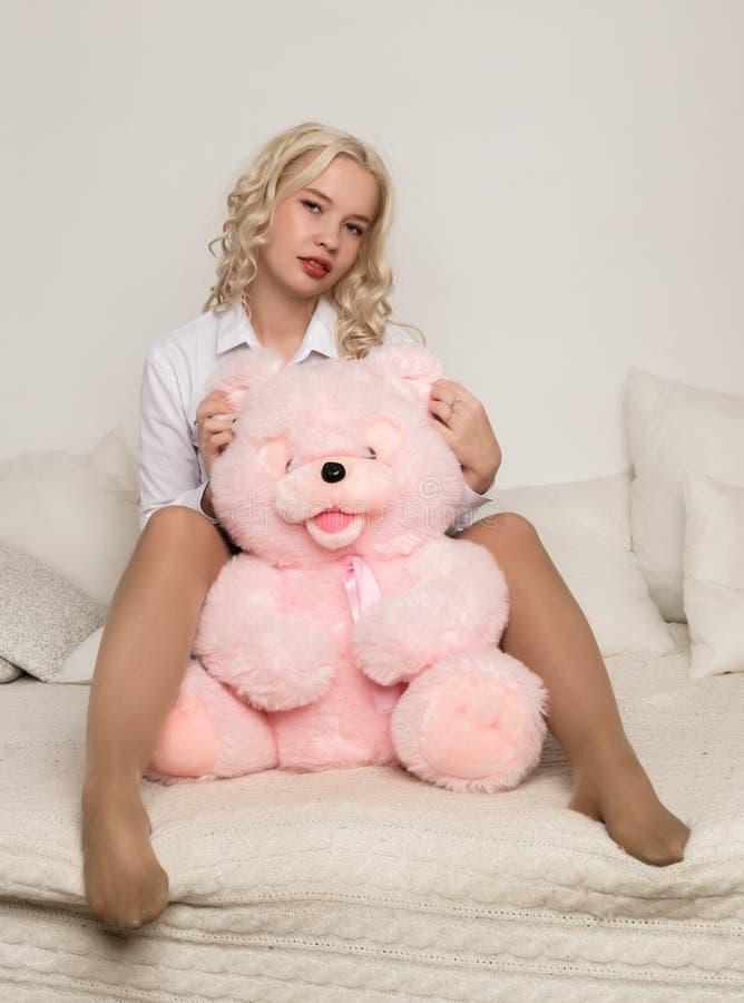 Glückliche schöne Blondine, die einen Teddybären umarmen Konzept des Feiertags oder des Geburtstages lizenzfreie stockfotografie