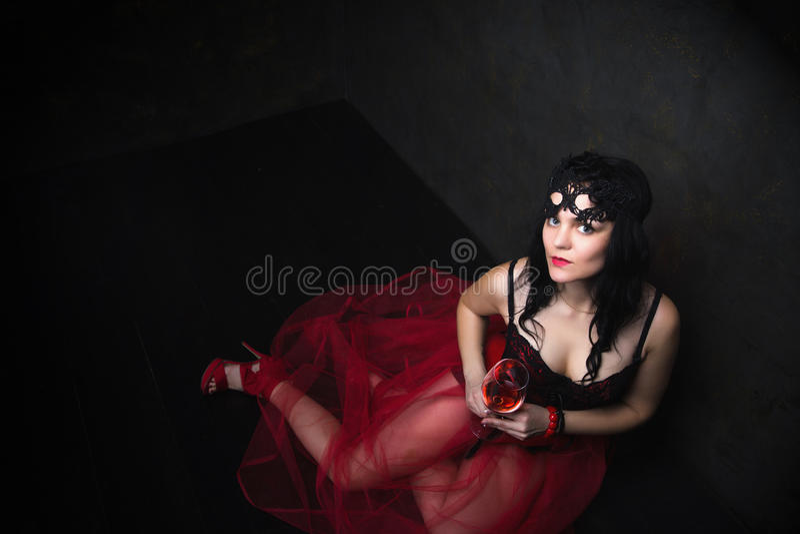 Glückliche schöne Brunettefrau im Korsett und im langen Haar mit glas lizenzfreies stockfoto