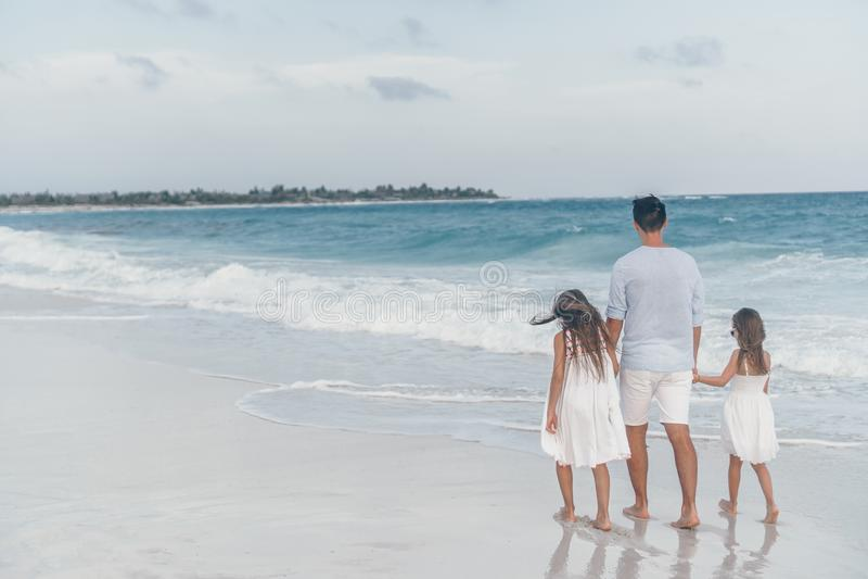 Glückliche schöne Familie des Vatis und der Kinder auf weißem Strand stockfotos