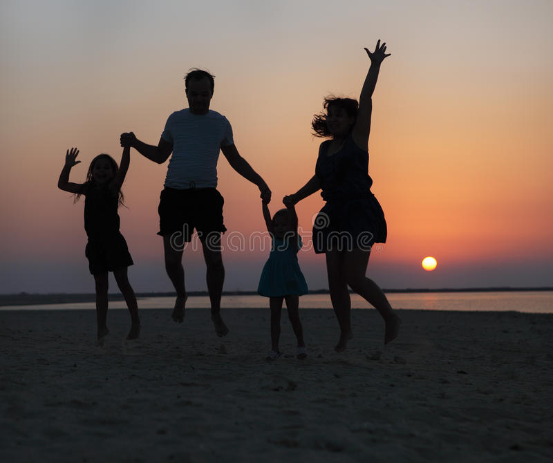 Glückliche schöne Familie, die auf den Strand bei dem Sonnenuntergang springt stockfotos