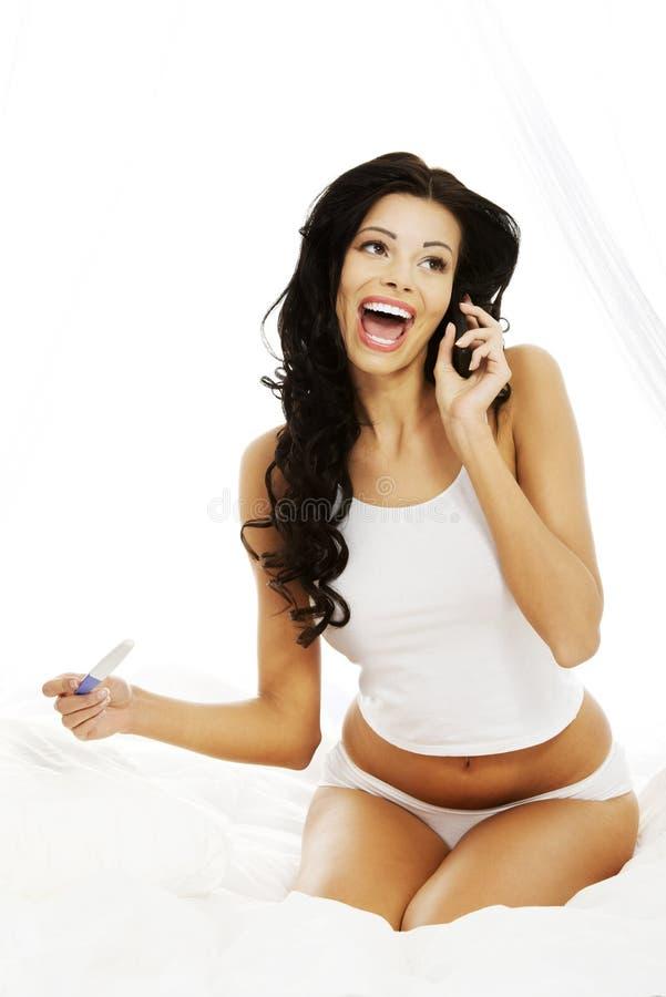 Glückliche schöne Frau auf Bett mit Schwangerschaftprüfung lizenzfreie stockfotos