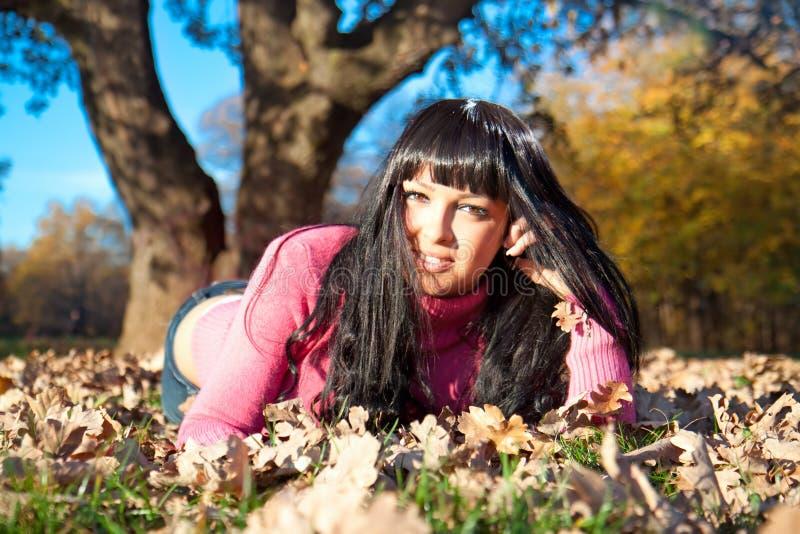 Glückliche schöne Frau, die im Herbstpark liegt lizenzfreies stockbild