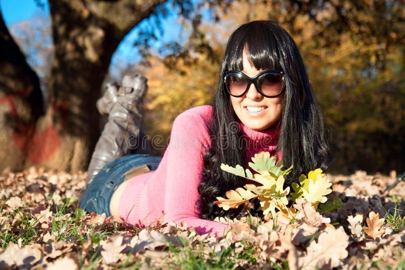 Glückliche schöne Frau, die im Herbstpark liegt lizenzfreie stockfotos
