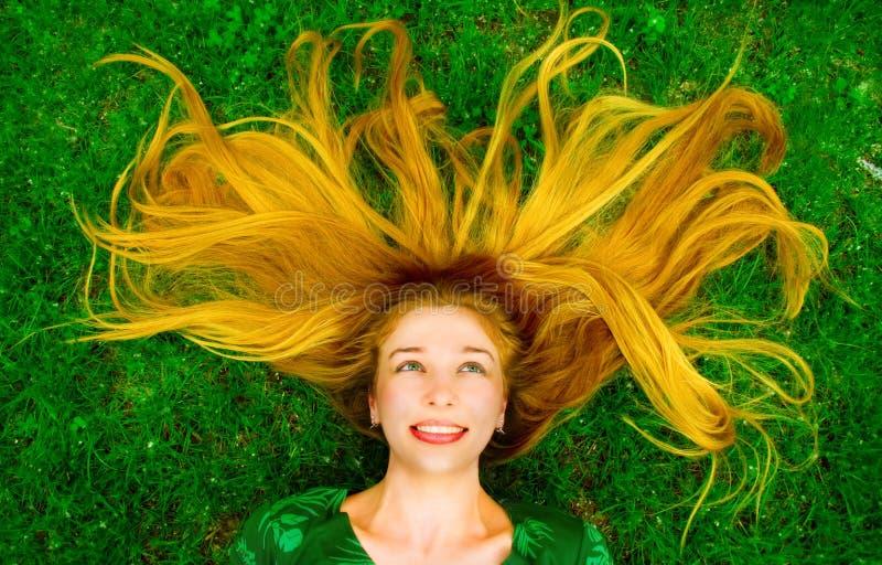 Glückliche schöne Frau im Gras lizenzfreie stockfotografie