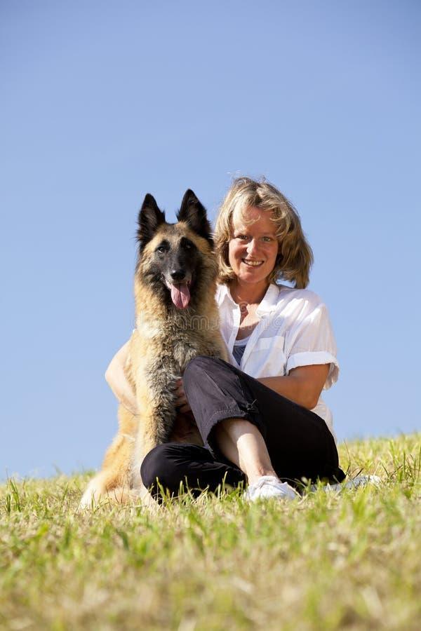 Glückliche schöne Frau mit belgischem Schäferhund stockfotos