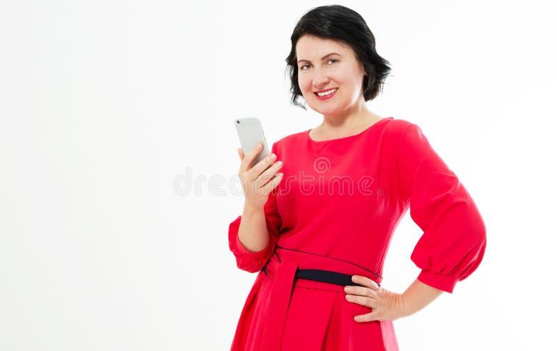 Glückliche schöne Frau von mittlerem Alter im roten Kleid benutzt ihr Telefon Bezaubernde brunette Frau, die im Internet plaudert lizenzfreie stockfotos
