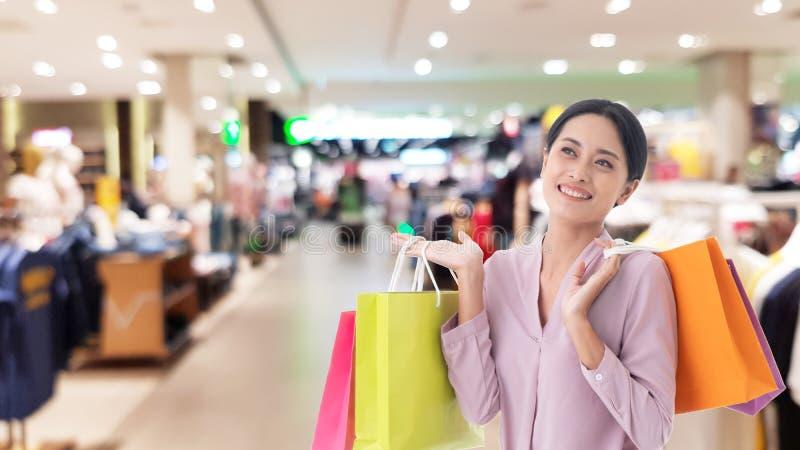 Glückliche schöne Hand des Asiatinlächelns zwei, die Einkaufstaschen hält stockbilder