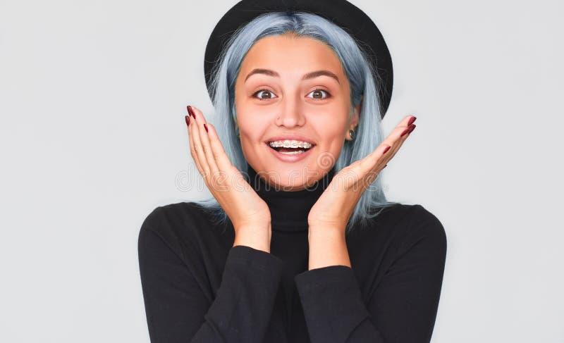Glückliche schöne Jugendliche, die schwarzen Hut mit dem blauen Haar lächelnd mit überrascht, voll von der Freude und vom Glück t stockbild