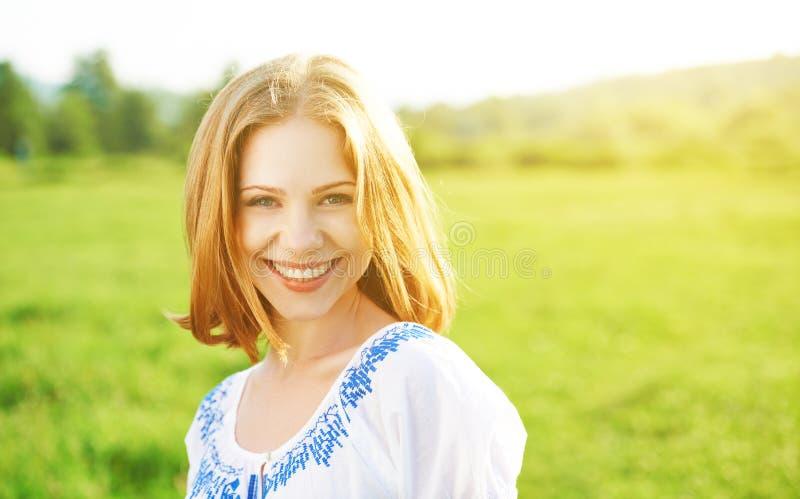 Glückliche schöne junge Frau, die auf Natur lacht und lächelt stockfotos